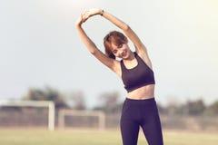 Giovane allenamento femminile prima di addestramento di forma fisica al parco Immagini Stock Libere da Diritti