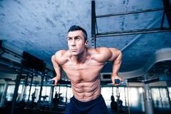 Giovane allenamento muscolare dell'uomo sulle barre Fotografia Stock