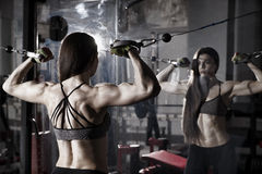 Giovane allenamento sexy della donna di forma fisica con la macchina di addestramento nella palestra Immagine Stock