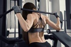 Giovane allenamento sexy della donna di forma fisica con la macchina di addestramento nella palestra Fotografia Stock Libera da Diritti