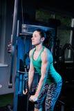 Giovane allenamento sexy della donna di forma fisica con la macchina di addestramento nella palestra Fotografia Stock