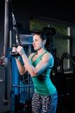 Giovane allenamento sexy della donna di forma fisica con la macchina di addestramento nella palestra Immagine Stock Libera da Diritti