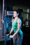 Giovane allenamento sexy della donna di forma fisica con la macchina di addestramento nella palestra Fotografie Stock Libere da Diritti