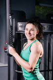 Giovane allenamento sexy della donna di forma fisica con la macchina di addestramento nella palestra Immagini Stock Libere da Diritti