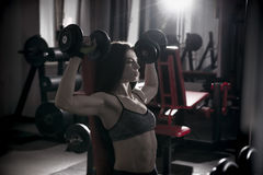 Giovane allenamento sexy della donna di forma fisica con le teste di legno nella palestra Fotografia Stock