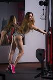 Giovane allenamento sexy della ragazza di forma fisica con l'istruttore nella palestra, donna con l'ente muscolare perfetto Fotografia Stock