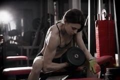 Giovane allenamento sexy della ragazza di forma fisica con le teste di legno nella palestra Donna castana di forma fisica nell'us Fotografia Stock