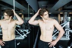 Giovane allenamento sexy muscolare dell'uomo in palestra vicino alle ombre dello specchio Immagini Stock Libere da Diritti
