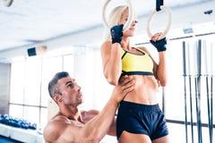 Giovane allenamento sportivo della donna sugli anelli di forma fisica Fotografia Stock Libera da Diritti