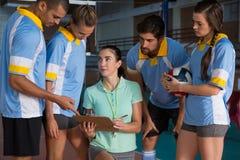 Giovane allenatore femminile che parla con i giocatori di pallavolo Fotografia Stock Libera da Diritti