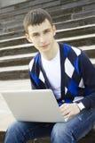 Giovane allievo che lavora ad un computer portatile Fotografie Stock Libere da Diritti