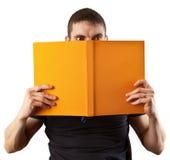 Giovane allievo che legge un libro spaventoso Fotografia Stock