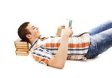 Giovane allievo che legge un libro sul pavimento Fotografie Stock Libere da Diritti