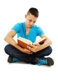 Giovane allievo che legge un libro sul pavimento Fotografia Stock