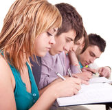 Giovane allievo che studia con i suoi amici Fotografie Stock
