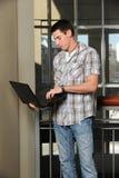 Giovane allievo che tiene un computer portatile Immagine Stock Libera da Diritti