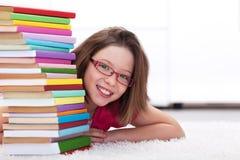 Giovane allievo con i lotti di sorridere dei libri Immagini Stock Libere da Diritti