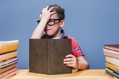 Giovane allievo con il libro che si siede allo scrittorio della scuola Immagine Stock Libera da Diritti