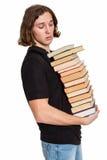 Giovane allievo con un mucchio dei libri Fotografia Stock Libera da Diritti
