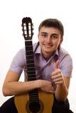 Giovane allievo con una chitarra su un bianco Fotografia Stock