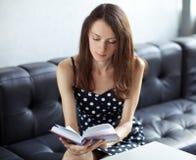Giovane allievo del brunette che legge un libro Immagini Stock Libere da Diritti