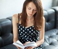 Giovane allievo del brunette che legge un libro Immagine Stock