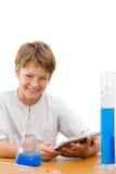 Giovane allievo di scienza con il ridurre in pani che fa lavoro. Fotografie Stock Libere da Diritti