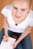 giovane allievo femminile che cattura le note mentre studiando Fotografia Stock Libera da Diritti