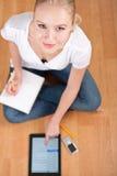 Giovane allievo femminile che cattura le note mentre studiando Fotografie Stock Libere da Diritti