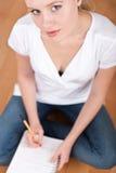 Giovane allievo femminile che cattura le note mentre studiando Immagine Stock