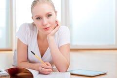 Giovane allievo femminile che cattura le note mentre studiando Immagini Stock