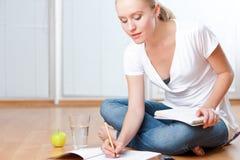 Giovane allievo femminile che cattura le note mentre studiando Fotografie Stock