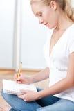 Giovane allievo femminile che cattura le note mentre studiando Immagine Stock Libera da Diritti