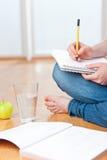Giovane allievo femminile che cattura le note mentre studiando Fotografia Stock