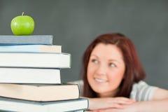 Giovane allievo femminile con una pila di libri Fotografia Stock Libera da Diritti