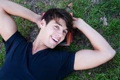 Giovane allievo maschio che si trova sull'erba con i libri Immagine Stock