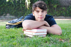 Giovane allievo maschio che si trova sull'erba con i libri Fotografie Stock