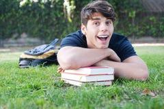 Giovane allievo maschio che si trova sull'erba con i libri Immagini Stock Libere da Diritti