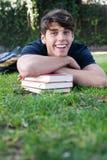 Giovane allievo maschio che si trova sull'erba con i libri Fotografie Stock Libere da Diritti