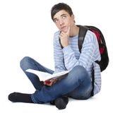 Giovane allievo maschio contemplativo con il libro Fotografie Stock Libere da Diritti