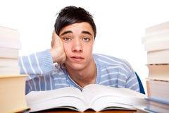 Giovane allievo maschio frustrato fra i libri di studio Fotografia Stock