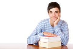 Giovane allievo maschio sorridente felice con i libri di studio Fotografia Stock