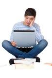 Giovane allievo sollecitato con i libri ed il computer portatile Immagini Stock Libere da Diritti