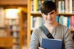 Giovane allievo sorridente che tiene un libro Fotografia Stock Libera da Diritti