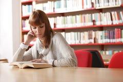 Giovane allievo in una libreria Fotografia Stock Libera da Diritti