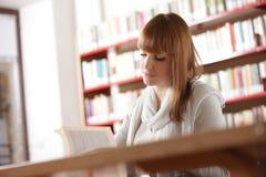 Giovane allievo in una libreria Fotografia Stock