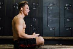 Giovane allo spogliatoio della palestra Tipo bello allo studio di forma fisica che fa il loro proprio personale prima della forma Fotografia Stock