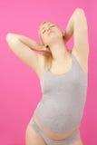 Giovane allungamento della donna incinta Fotografia Stock