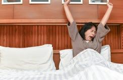 Giovane allungamento della moglie e sbadigliare a letto Fotografia Stock