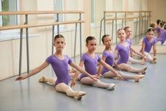Giovane allungamento delle ballerine che si siede sul pavimento Immagine Stock